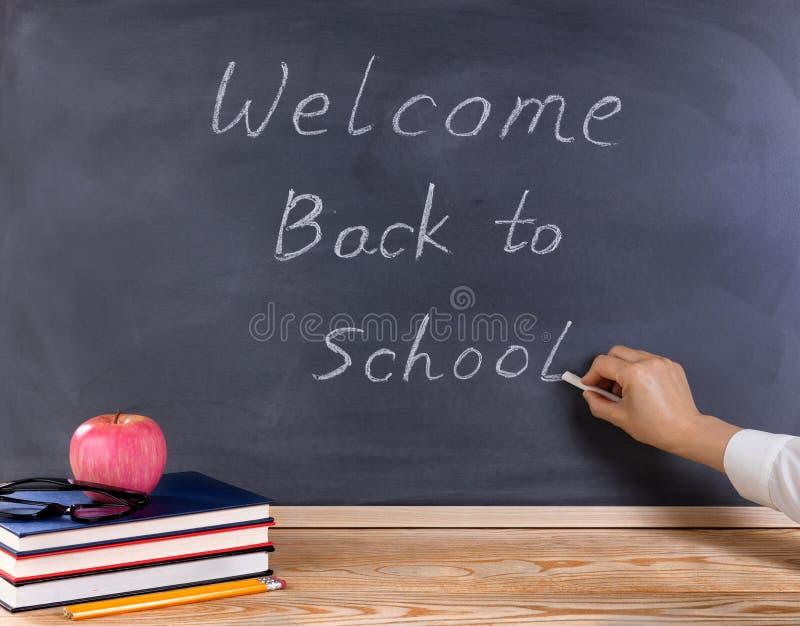老师回到学校的文字欢迎删掉的黑chalkboar的 免版税库存图片