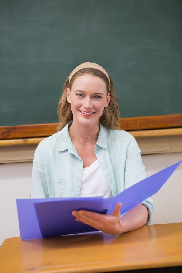 老师在她的书桌的读书纸 库存图片