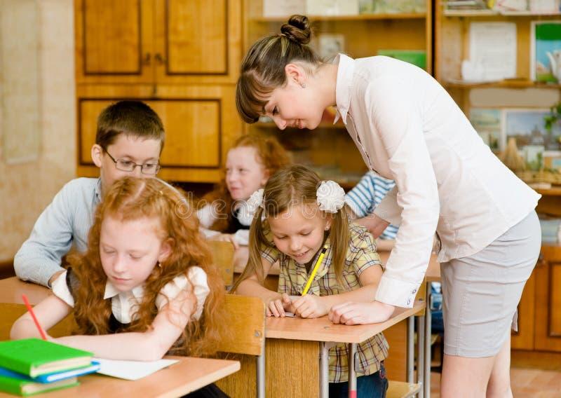 老师在教室帮助有schoolwork的schoolkids 免版税库存照片