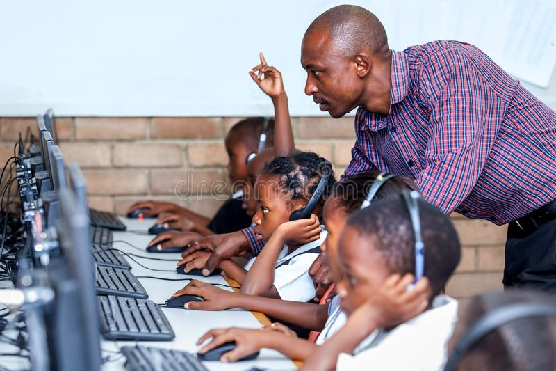 老师在显示孩子计算机技能的教室 库存图片