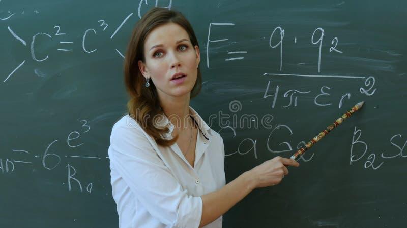 老师在黑板背景的教室解释某事在phisics 免版税库存图片