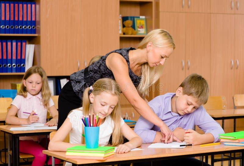 年轻老师帮助小学的学生检查的 免版税库存照片