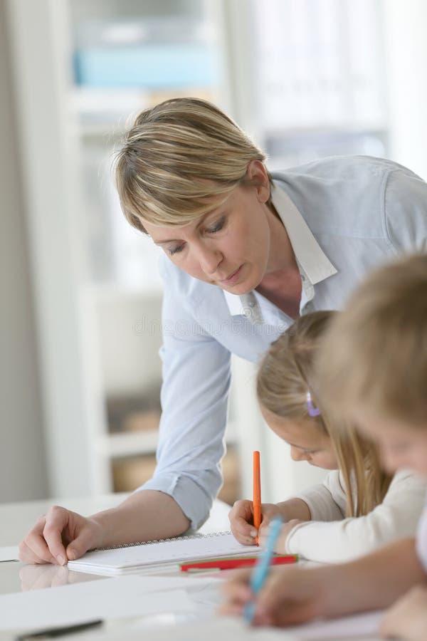 老师帮助的学生在教室 库存图片