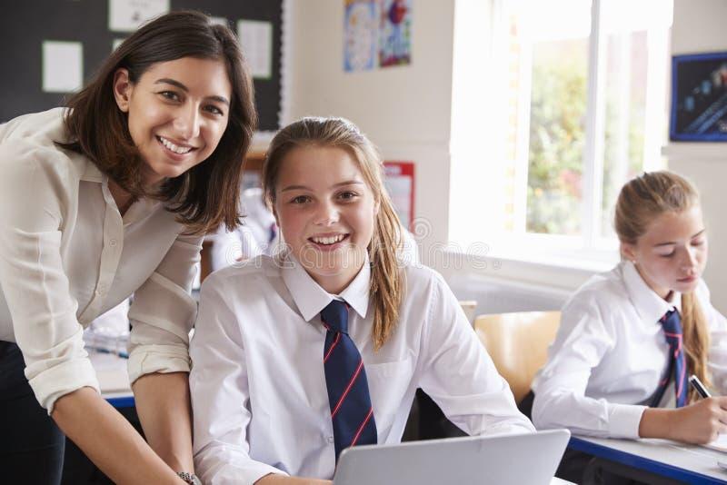 老师帮助的学生画象使用计算机的在教室 免版税库存照片