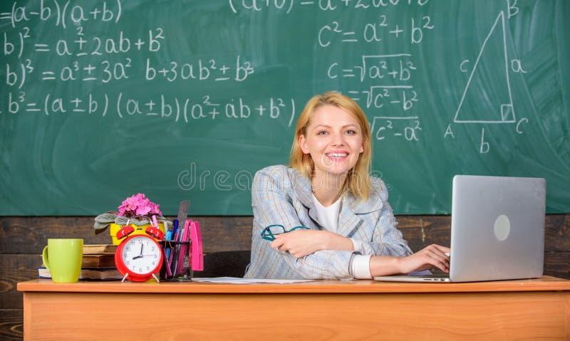 老师快乐的宜人的妇女教育家坐桌教室与膝上型计算机一起使用 在学校黑板的老师愉快的工作 免版税库存图片