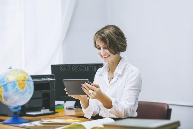 老师愉快的少妇在有电子片剂的一间教室 库存照片