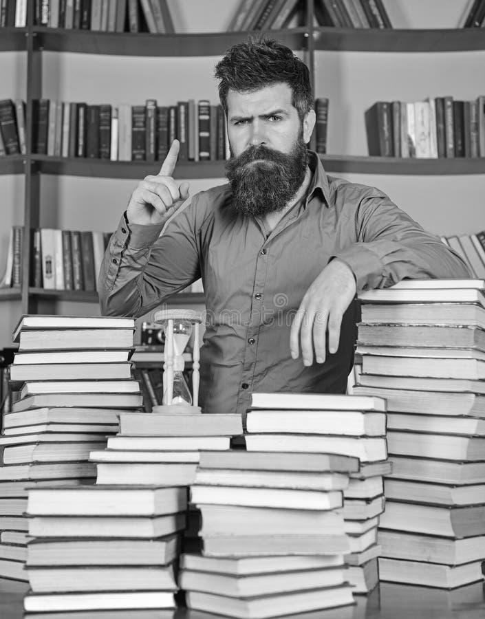 老师或学生有胡子的站立在桌上与书, defocused 图书管理员概念 确信的面孔立场的人 免版税图库摄影