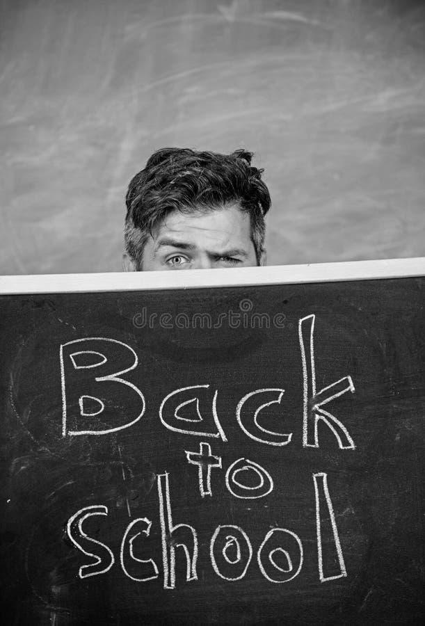 老师或校长在题字后回到学校 偷看在黑板外面的老师 掩藏的教育家后边 库存图片