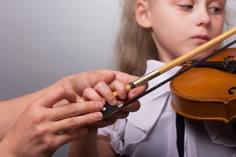 老师改正教小提琴的女孩的手 免版税库存照片