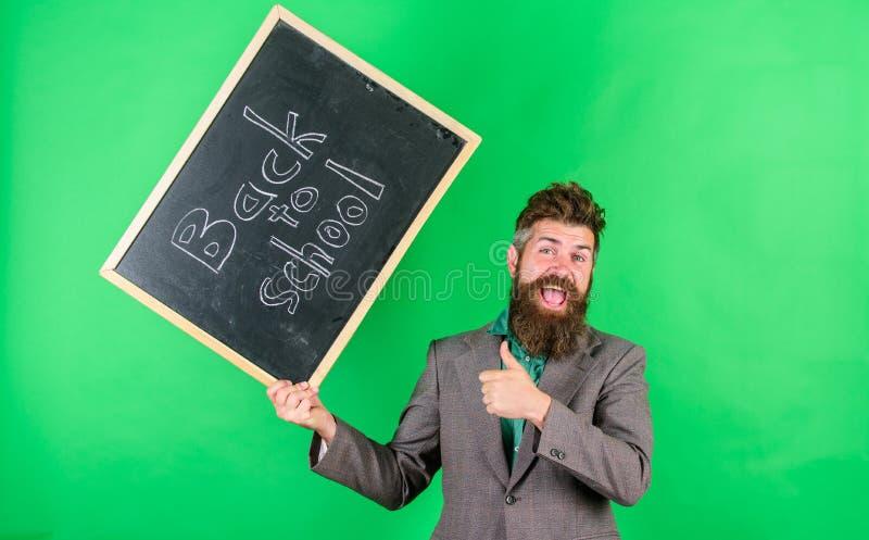 老师有胡子的人拿着有题字的黑板回到学校绿色背景 老师愉快快乐 库存照片