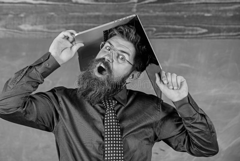 老师有胡子的人有现代膝上型计算机黑板背景 学校使他惊奇 行家老师积极与 免版税库存照片
