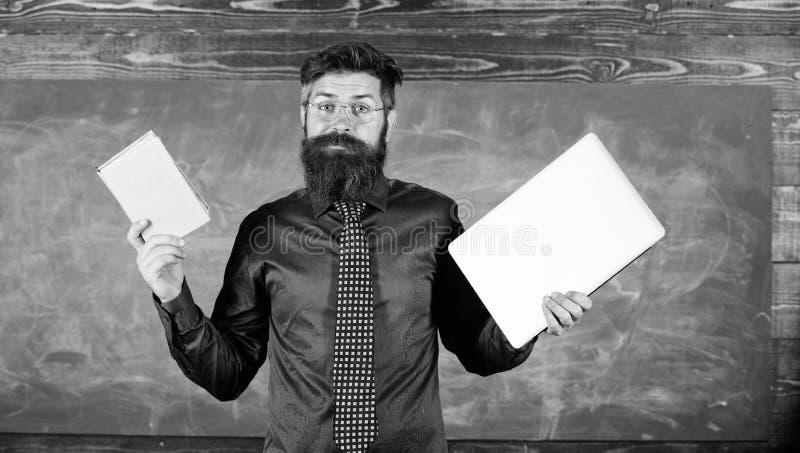 老师有胡子的行家拿着书和膝上型计算机 选择正确的教学方法 现代过时 老师选择 库存图片