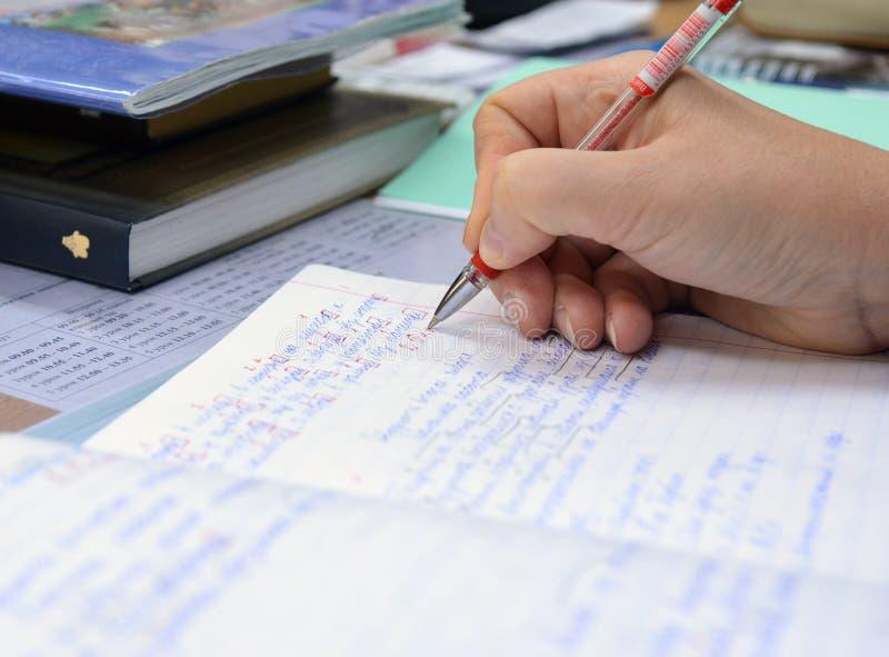老师检查笔记本与评估和曝光任务  免版税图库摄影