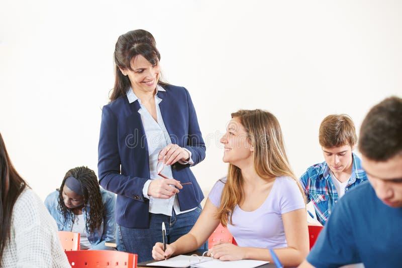 老师监督她的学生` s检查 库存图片