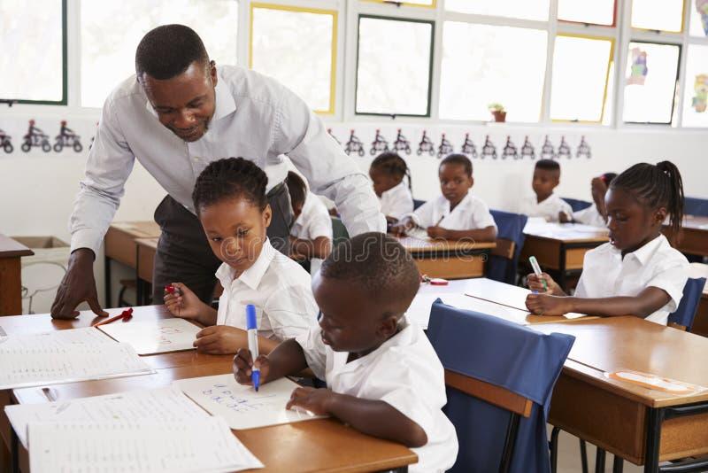 老师站立帮助的小学孩子在他们的书桌 免版税库存照片