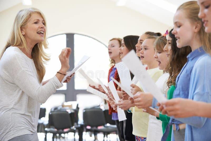 老师被鼓励的唱歌的小组的孩子 免版税库存照片