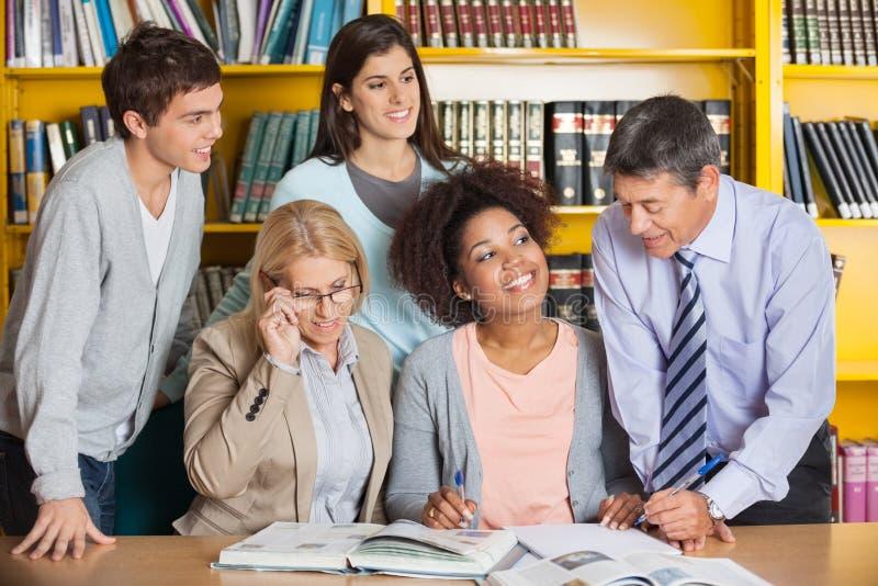 老师谈论与学生在图书馆 免版税图库摄影