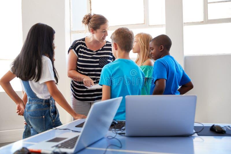 老师谈话与小组在学会学校电脑的类以后的学生编码 免版税库存图片