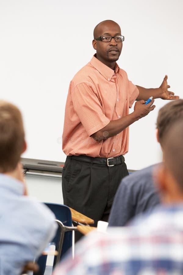 老师谈话与站立在Whiteboard前面的类 免版税库存照片