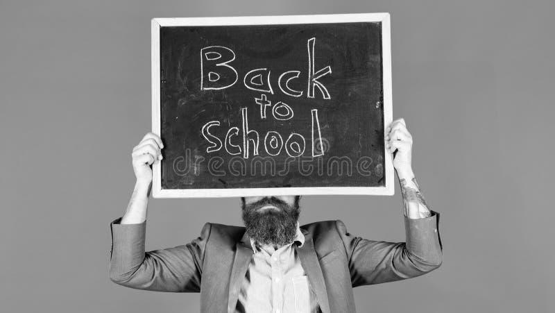 老师通知关于学期起点 老师有胡子的人拿着有题字的黑板回到学校蓝色 库存图片