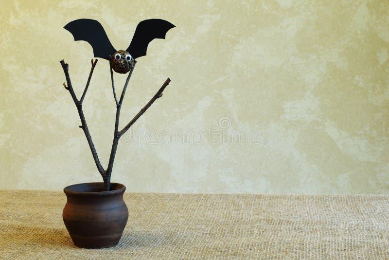 老干燥分支和棒从冷杉球果和黑纸板在黏土花瓶在手织的黄麻织品对轻的墙壁 E 免版税库存照片