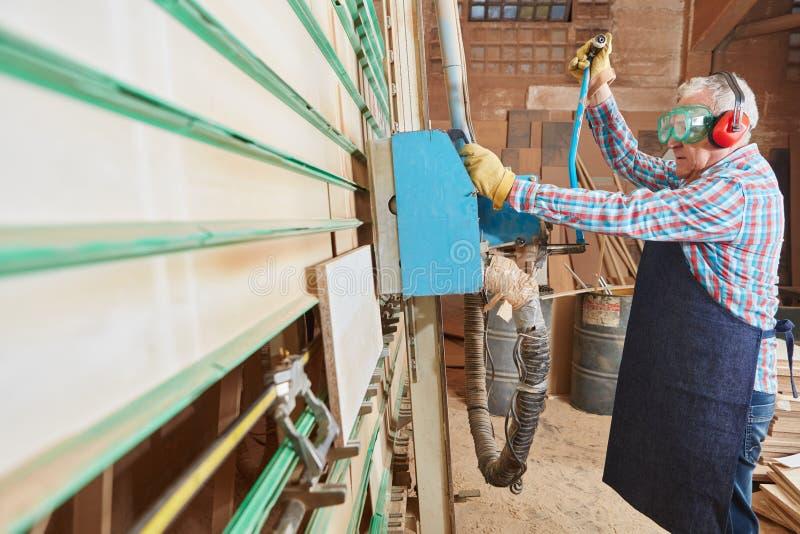 老年人与板材垂直的锯一起使用 库存图片