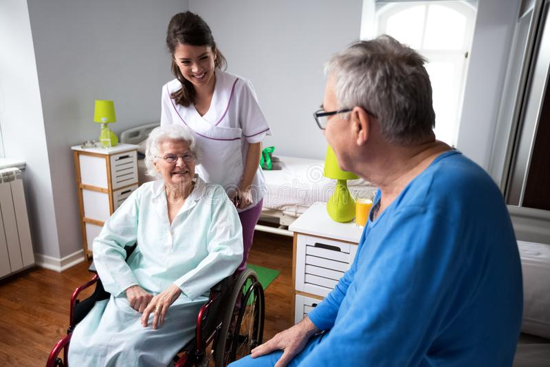 老年人的年轻微笑的护士关心 图库摄影