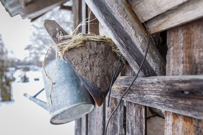 老庭院意义重大和一把老锄在墙壁上垂悬了在冬天 免版税库存照片