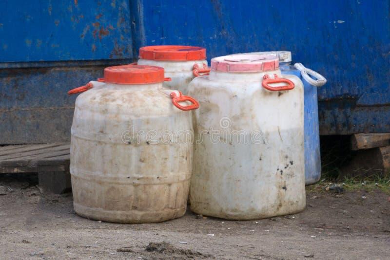 老建筑器材例如白色能和蓝色塑料桶 图库摄影