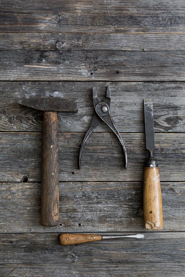 老建筑用工具加工锤子,钳子,螺丝刀,在暗色年迈的木板的凿子谎言与传神纹理的 图库摄影