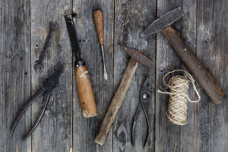 老建筑用工具加工锤子,钳子,螺丝刀,在暗色年迈的木板的凿子谎言与传神纹理的 免版税库存照片