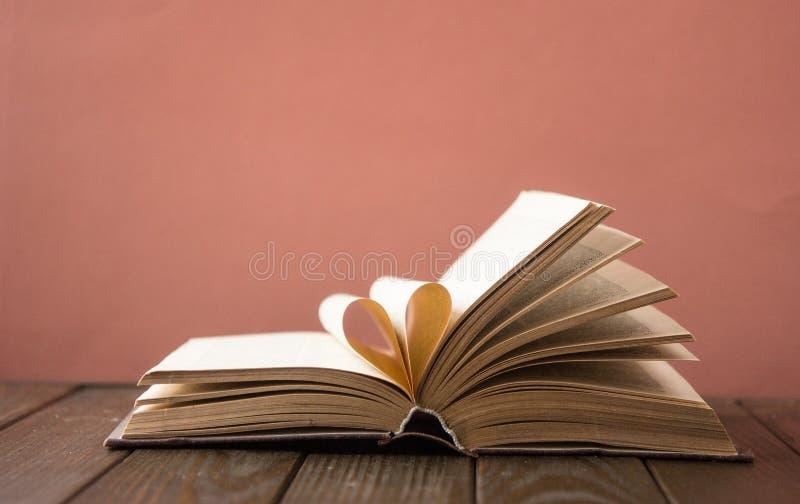 老开放精装书书,页装饰入爱的心脏形状在华伦泰` s 与开放书心脏的爱 库存照片