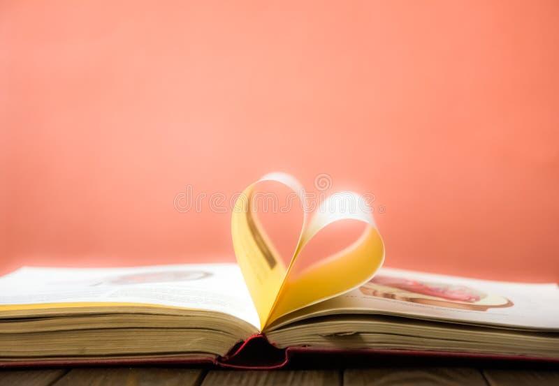 老开放精装书书,页装饰入爱的心脏形状在华伦泰` s 与开放书心脏的爱 库存图片