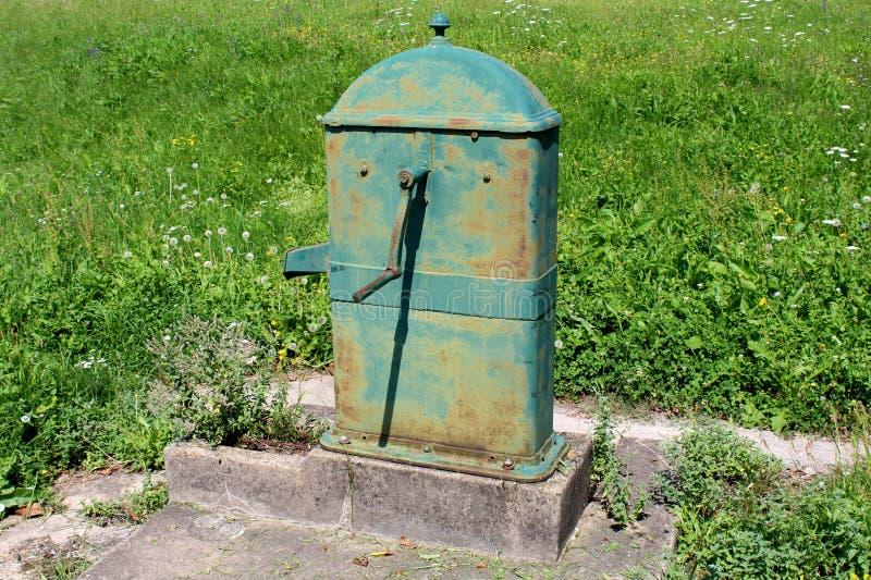 老很少使用了有在具体立场登上的大转动的把柄的生锈的室外金属水泵 免版税库存图片