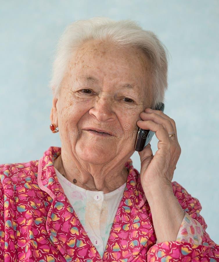 老微笑的妇女谈话在手机 免版税库存照片