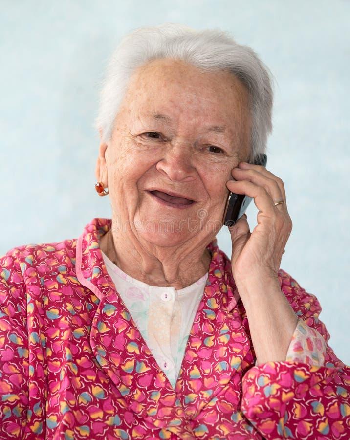 老微笑的妇女谈话在电话 图库摄影