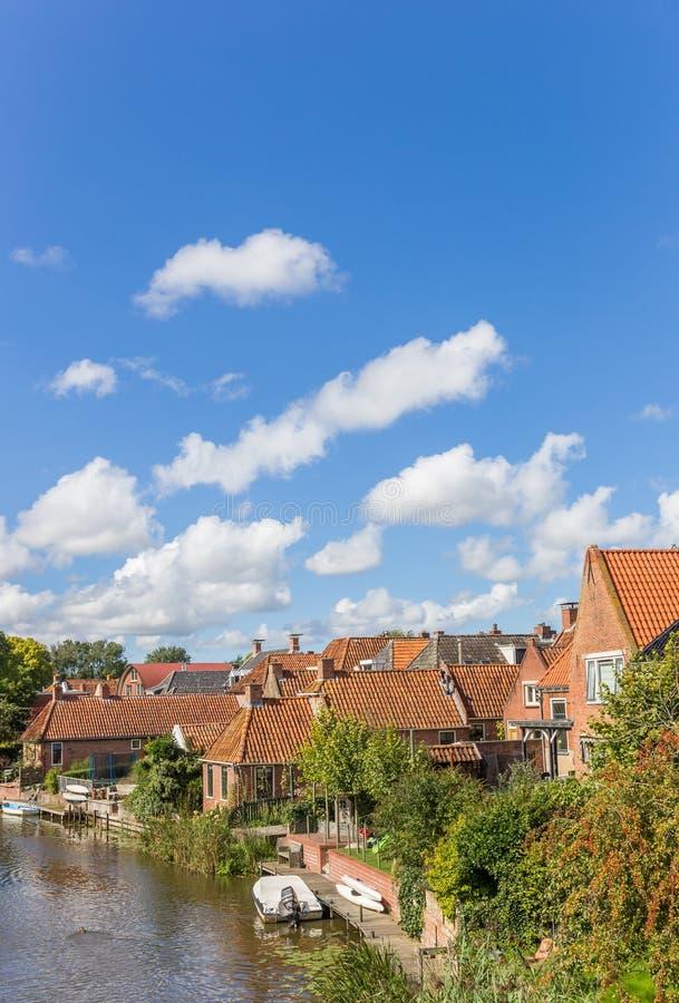老房子和河在Winsum村庄  库存图片