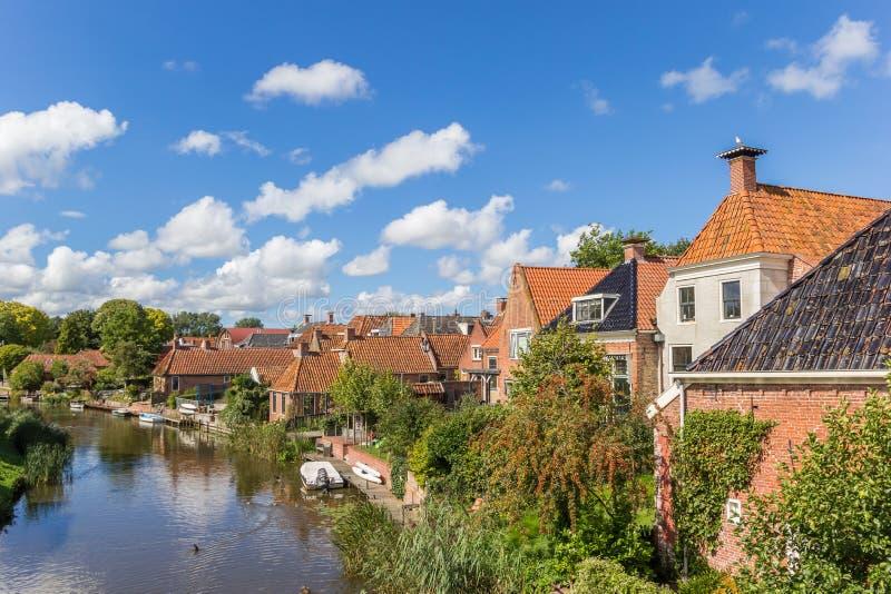 老房子和河在Winsum村庄  图库摄影