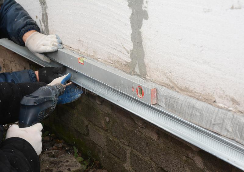 老房子基础墙壁修理和整修与安装金属板防水的和保护免受雨 免版税库存图片