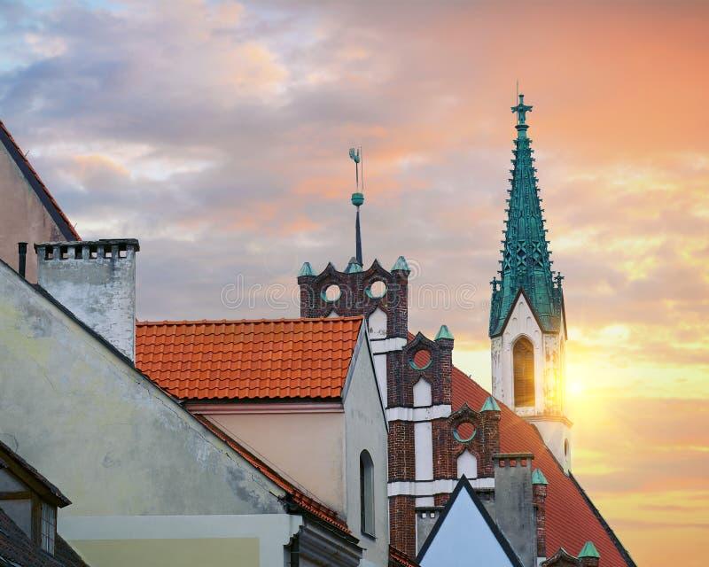 老房子红色屋顶Skarnu iela街道的有圣约翰斯教会的在背景里加,拉脱维亚中 图库摄影