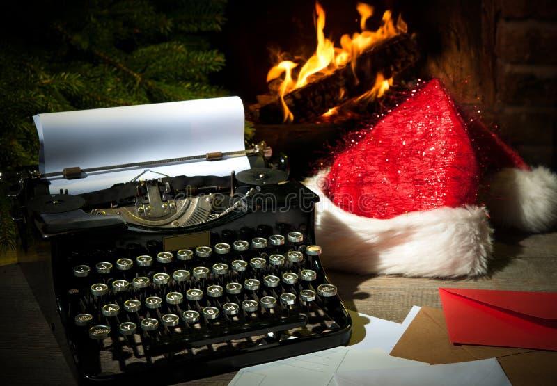 老打字机和圣诞老人帽子在书桌上 库存照片