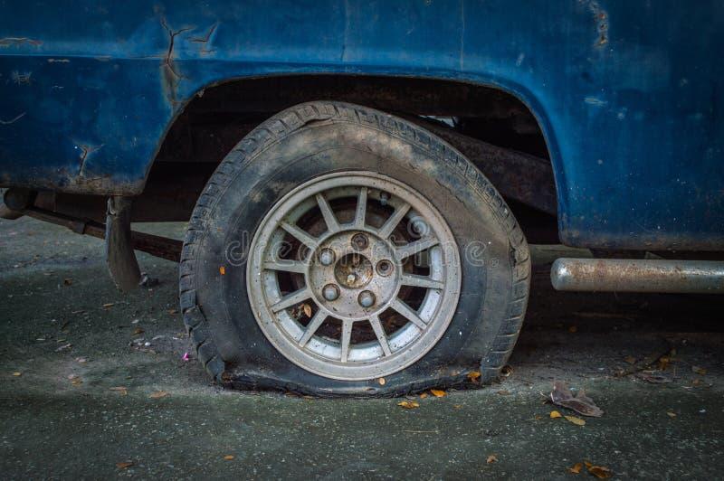 老打破的生锈的汽车,在轮胎的焦点 免版税库存照片