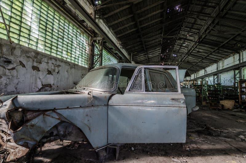 老打破的汽车在仓库 免版税库存图片