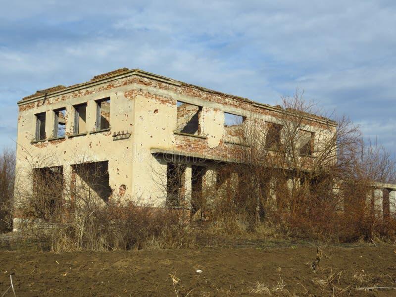 老拆毁了被放弃的大厦长满与灌木和灌木 免版税库存照片