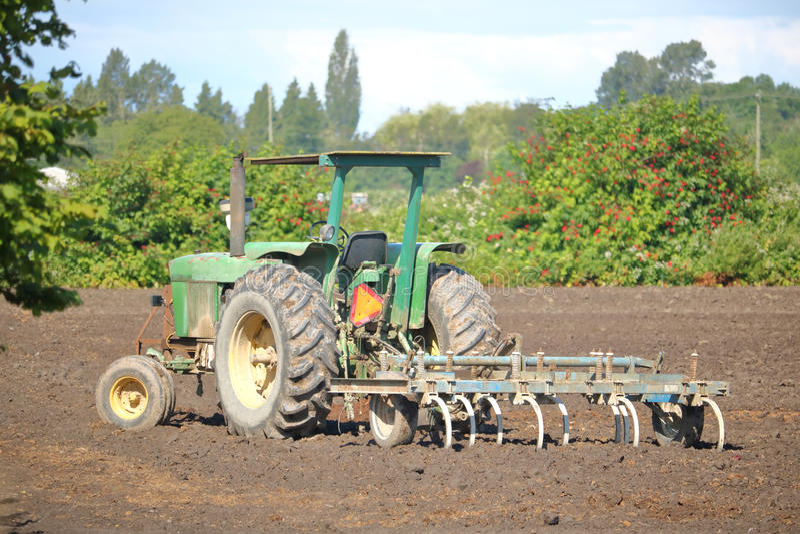 老拖拉机和犁在领域 免版税图库摄影