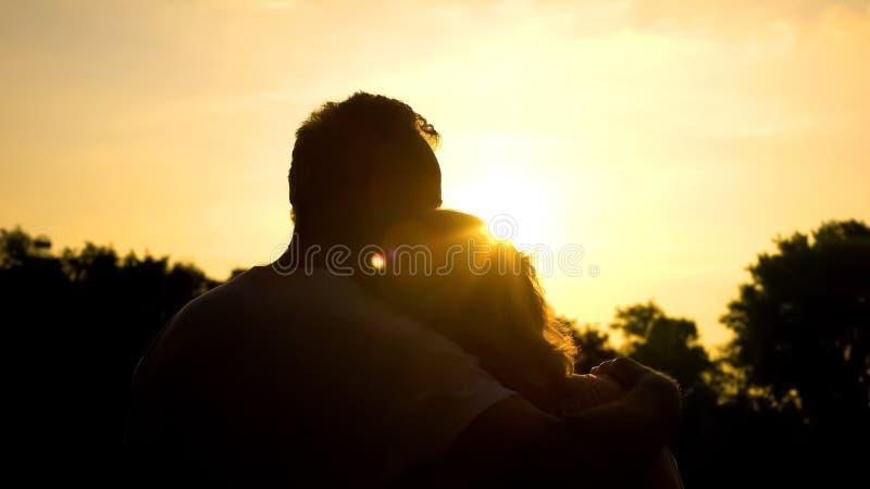 老拥抱的夫妇,观看的日落剪影一起,安全晚年 免版税图库摄影