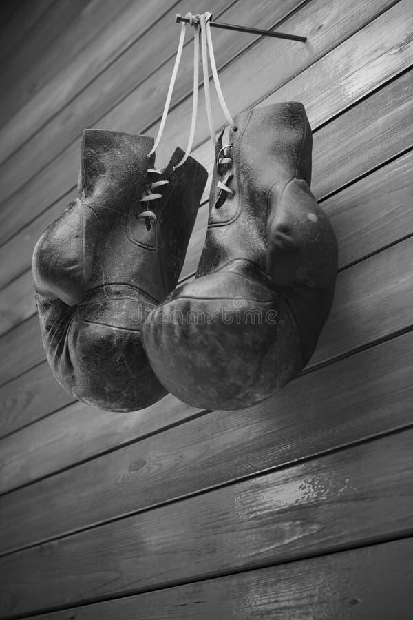 老拳击手套在木墙壁上的钉子垂悬有文本的拷贝空间的 高分辨率3D回报 库存照片