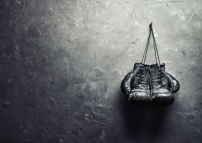老拳击手套在纹理墙壁上的钉子垂悬 免版税库存图片