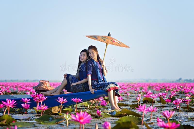 老挝妇女在花莲花湖,佩带传统泰国人,红色莲花海UdonThani泰国的妇女 库存图片