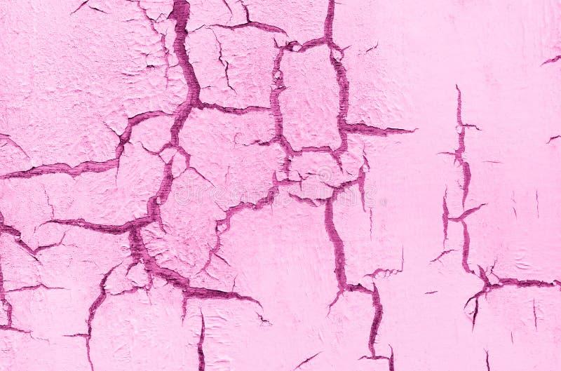 老损坏的破裂的油漆墙壁,难看的东西背景,桃红色淡色 免版税库存照片